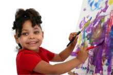 A young girl painting using two paint brushes
