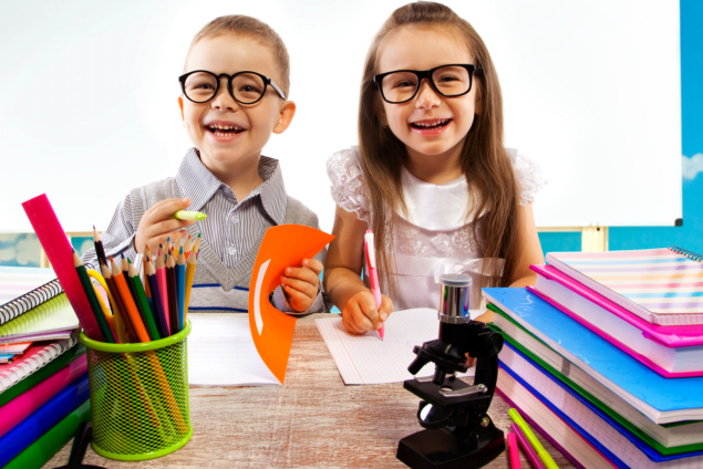 A young boy and girl writing on a notebook